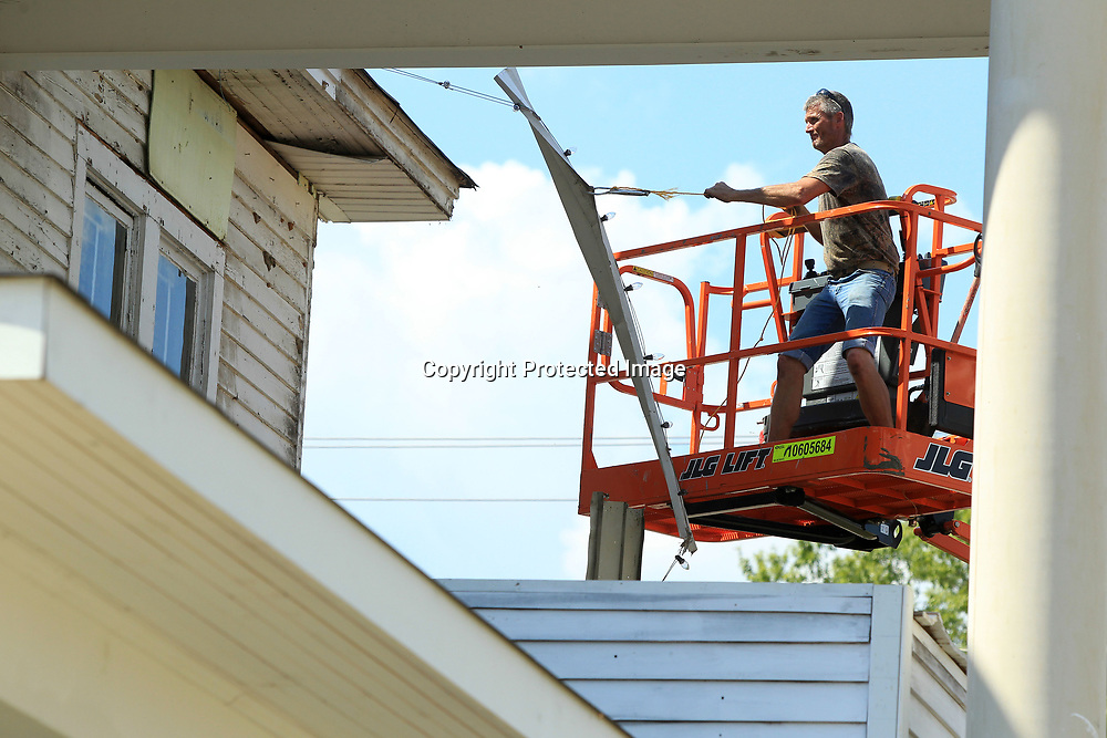 David Scruggs, an employee for Wooten Construction, pull old aluminum siding off of the Spain House in Tupelo on Thursday as the crew works to prep the home for new siding.