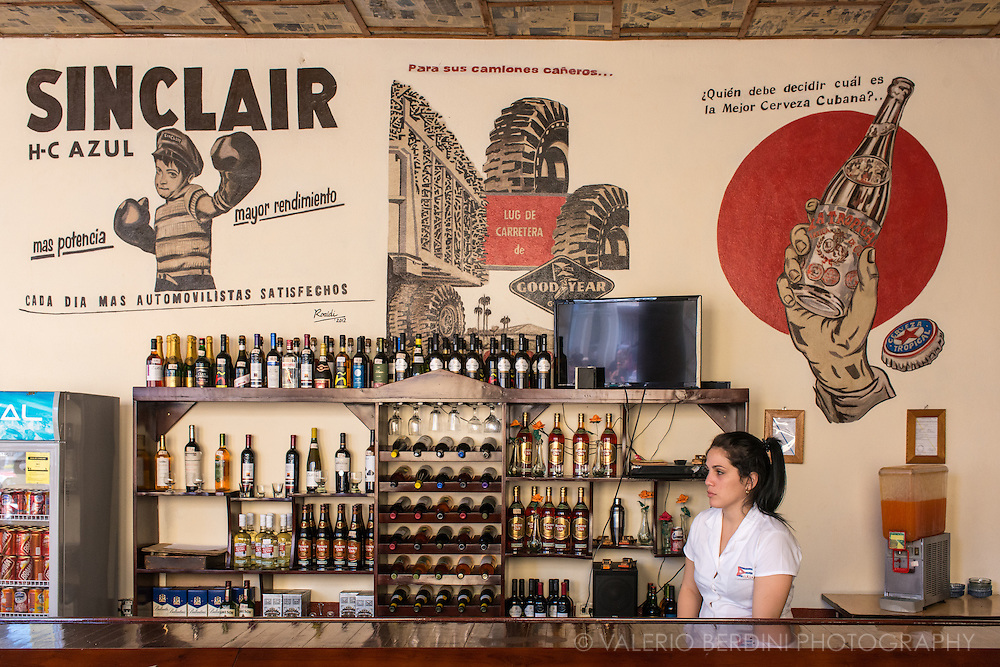 A girl waits for customer in a bar of Remedios selling alcoholic and soft drinks. Cuba, 2015.<br /> <br /> This photo has been published on the Guardian online (10 Apr 2016)and in print (11 Apr 2016)http://www.theguardian.com/world/2016/apr/10/cuba-running-low-on-beer-as-thirsty-us-tourists-descend