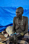 An impoverished woman living in lean to just outside the wall of a large, open terrain opposite John Garang's tomb in Juba. The area is contaminated with thousands of unexploded ordinance leftover from Sudan's long civil war. The Government of South Sudan called on Mines Advisory Group (MAG) to clear the area and make it safe for the thousands of people and dignitaries who will be attending the declaration of independence on July 9th...Juba, South Sudan. 04/07/2011..Photo © J.B. Russell