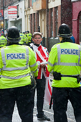 An EDL supporter wapped in the Union Flag looks back past police officers as they escort<br />
