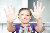 Girl (5-6) showing hands covered in flour portrait