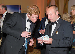 Prince Harry is shown some magic by former soldier Shane Sterling<br /> Prince Harry, Patron of the Walking With The Wounded South Pole Allied Challenge, attends the charity's Crystal Ball at the Grosvenor House Hotel, central London.<br /> The event hosted by Ben Fogle, with music Ellie Goulding and The Stereophonics. Also present were Olympian Matthew Pinsent CBE and Team Glenfiddich. The team of wounded service personnel will accompany the Prince on an expedition to the South Pole later this year, London,<br /> Thursday, 30th May 2013<br /> Picture by Anthony Upton / i-Images