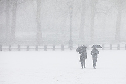 © Licensed to London News Pictures. 27/02/2018. London, UK. Two men take shelter beneath umbrellas as heavy snow falls on Horse Guards Parade in central London. Severe cold, blizzards and heavy snow are expected for the rest of the week as the 'Beast from the East' brings freezing Siberian air to the UK. Photo credit: Rob Pinney/LNP