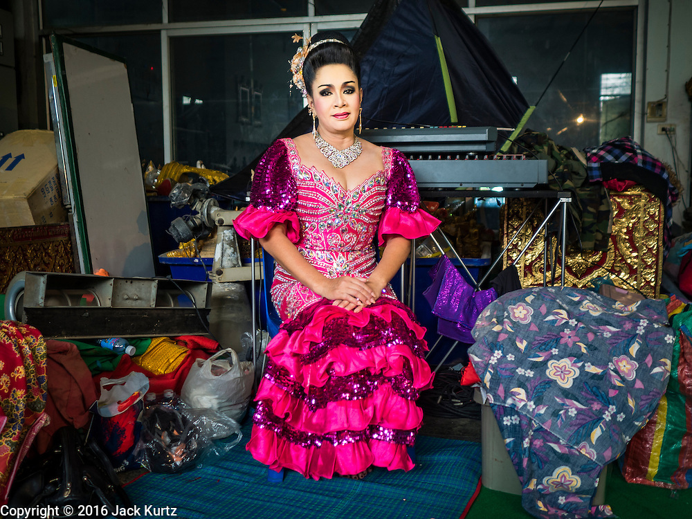 """30 JANUARY 2016 - NONTHABURI, NONTHABURI, THAILAND: A woman waits to take the stage during a """"likay"""" show at Wat Bua Khwan in Nonthaburi, north of Bangkok. Likay is a form of popular folk theatre that includes exposition, singing and dancing in Thailand. It uses a combination of extravagant costumes and minimally equipped stages. Intentionally vague storylines means performances rely on actors' skills of improvisation. Like better the known Chinese Opera, which it resembles, Likay is performed mostly at temple fairs and privately sponsored events, especially in rural areas. Likay operas are televised and there is a market for bootleg likay videos and live performance of likay is becoming more rare.     PHOTO BY JACK KURTZ"""