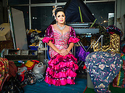"30 JANUARY 2016 - NONTHABURI, NONTHABURI, THAILAND: A woman waits to take the stage during a ""likay"" show at Wat Bua Khwan in Nonthaburi, north of Bangkok. Likay is a form of popular folk theatre that includes exposition, singing and dancing in Thailand. It uses a combination of extravagant costumes and minimally equipped stages. Intentionally vague storylines means performances rely on actors' skills of improvisation. Like better the known Chinese Opera, which it resembles, Likay is performed mostly at temple fairs and privately sponsored events, especially in rural areas. Likay operas are televised and there is a market for bootleg likay videos and live performance of likay is becoming more rare.     PHOTO BY JACK KURTZ"