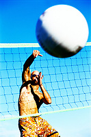 Man spiking a volleyball.