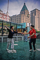 Two ladies practice their ballroom dancing on the Bund with the famous Peace Hotel in the background.