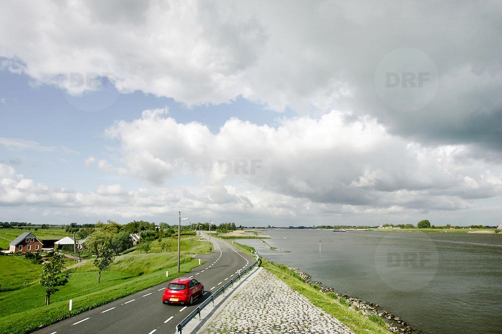 Nederland Bergambacht 29 mei 2006 20060529.Groene hart, auto rijdt over dijkweg langs de rivier de Lek in polderlandschap...Serie tbv Schieland en de Krimpenerwaard, deze zorgt als waterschap voor droge voeten en schoon water in een bepaald gebied. Het beheersgebied van Schieland en de Krimpenerwaard strekt zich uit tussen Rotterdam, Schoonhoven en Zoetermeer en is het laagste gebied in Nederland. Binnen dit gebied zorgt Schieland en de Krimpenerwaard voor de kwaliteit van het oppervlaktewater, het waterpeil en de waterkeringen. Daarnaast beheert Schieland en de Krimpenerwaard een aantal wegen in de Krimpenerwaard...Foto David Rozing/