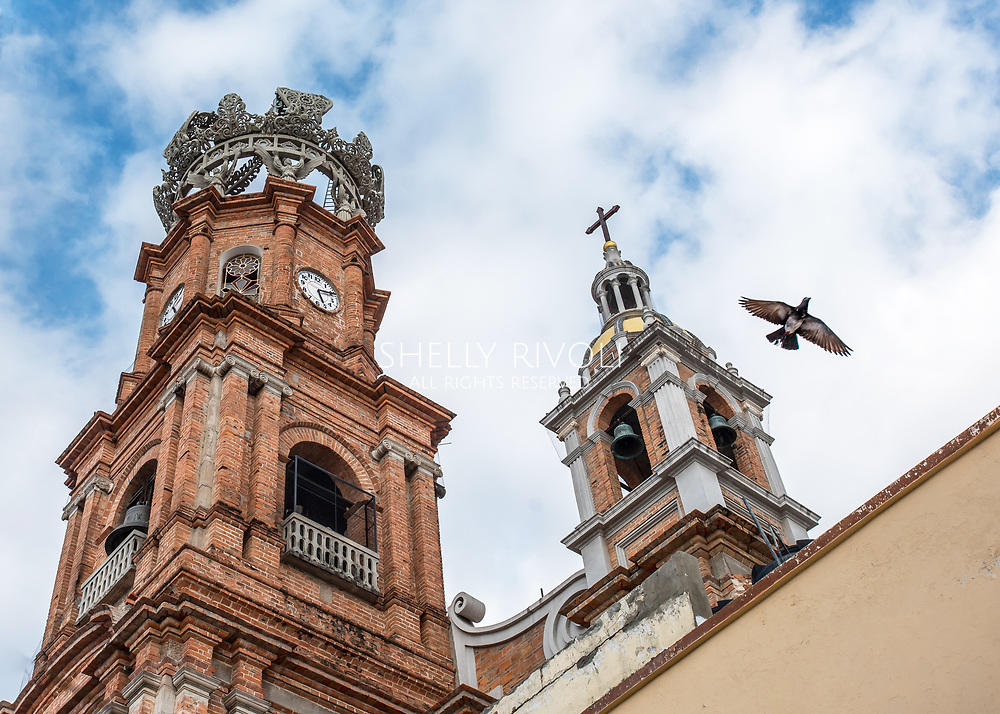 Bell towers of Our Lady of Guadalupe cathedral / church in Puerto Vallarta's old town as a bird flies against the sky as if symbolizing peace or hope