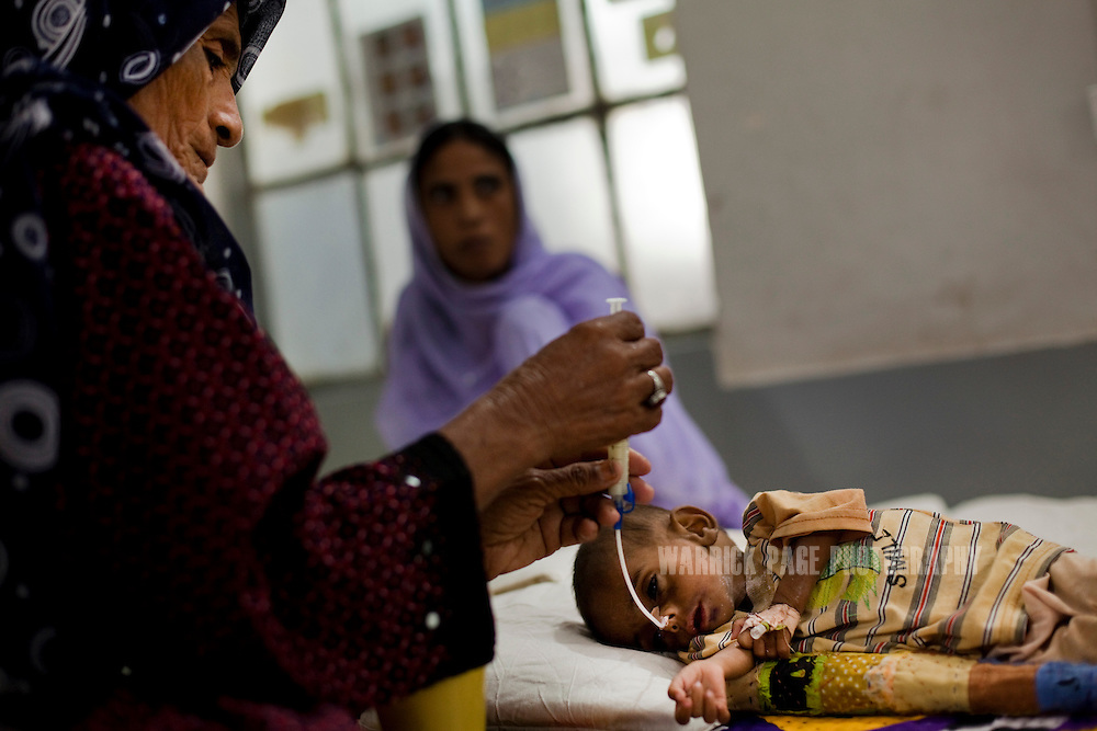 A woman feeds a severely malnourished baby, in the nutrition stabilisation centre in Jamsharoo Civil Hospital, on October 13, 2011, in Jamsharoo, Pakistan. According to UN reports, hundreds of thousands of children in Pakistan suffer from severe-acute-malnutrition, with 15.1% of children experiencing acute malnutrition. Child malnutrition has breached emergency levels in Pakistan's Sindh province, after monsoon floods devastated the country's poorest region for a second year. Extreme poverty, poor diet and health, exposure to disease, and inadequate sanitation and hygiene annually produce alarming levels of malnutrition amongst children, but the floods have increasingly endangered an already vulnerable population. (Photo by Warrick Page)