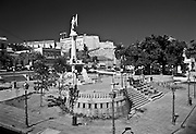 Wide view of the plaza with Columbus statue in the middle and Fort San Cristobal in the background
