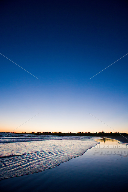 USA, Middletown, RI - Twilight falls through a cloudless sky over calm water at Sachuest Beach (2nd beach), a Newport favorite. The outline of St. George's provides the only landmark reference.