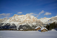 Mounts Lavarella and Conturines behind a pair of snow covered wooden barn at the Alta Badia ski resort near Corvara, The Dolomites, South Tyrol, Italy