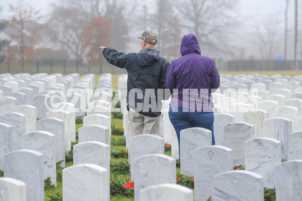 People walk through to lay wreaths at gravesites during Wreaths Across America Saturday, December 14, 2019 at Washington Crossing National Cemetery in Newtown, Pennsylvania. Thousands of wreaths are laid each year for Wreaths Across America by volunteers who gather and then place the wreaths at graves of veterans. (Photo by William Thomas Cain / CAIN IMAGES)