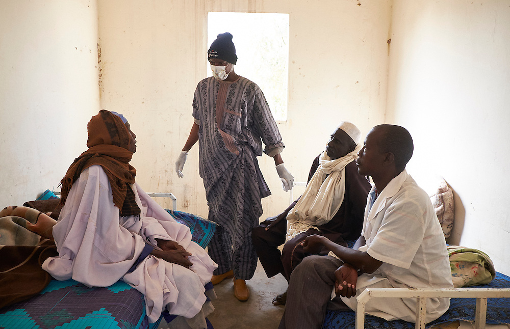Nurse Harouna Hamza (right) with patients at the medical centre in the village of Boudoum near the border with Nigeria on the outskirts of Diffa, Niger on February 13, 2016. Displaced people from Niger and Nigeria are sheltering in the village after fleeing frequent attacks at the nearby border, less than a kilometre away. An attack by Boko Haram on the Nigerien army had taken place two days before. <br /> <br /> 'Boko Haram came and told me to treat their wounded combattants. They said if I did not they would cut my throat. I knew who they were, they come from this village, they are Nigeriens. They have been back multiple times and always threatened to kill me.'