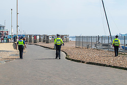 © Licensed to London News Pictures.12/04/2020. Brighton, UK. Police officers patrol the beach and promenade in Brighton and Hove on Easter Sunday as the Coronavirus Lockdown continues. Only a handful of people can be seen outside in the seaside resort. Photo credit: Hugo Michiels/LNP