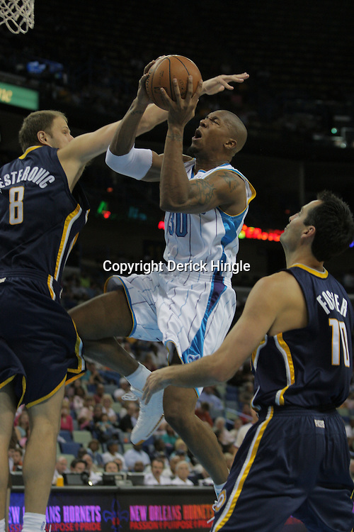 21 October 2008:  New Orleans Hornets forward David West (30) drives the lane between Rasho Nesterovic (8) and Jeff Foster (10) during a NBA preseason game between the Indiana Pacers and the New Orleans Hornets at at the New Orleans Arena in New Orleans, LA..