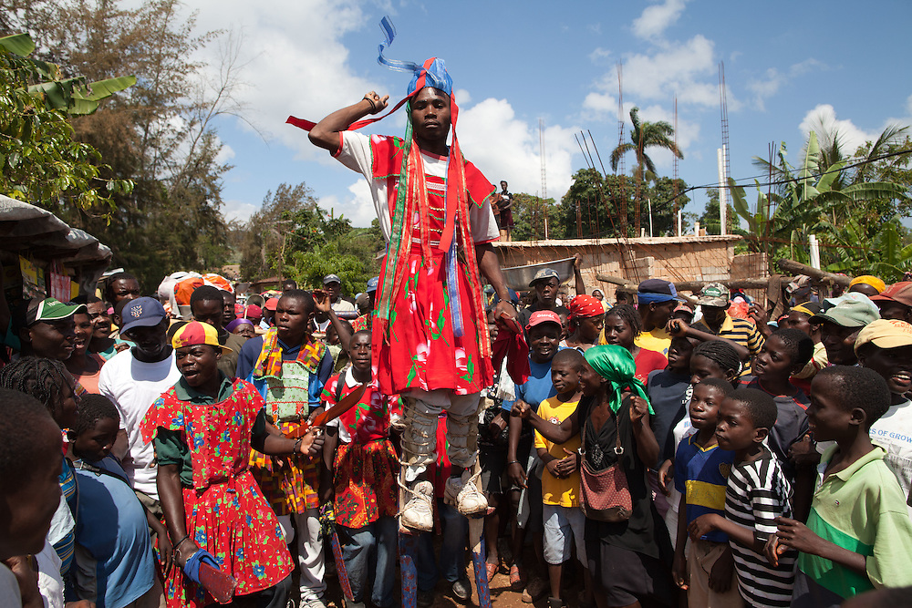 A man dancing on stilts leads a street band though  an open-air market celbrating Easter Monday also known as Renewal Monday.