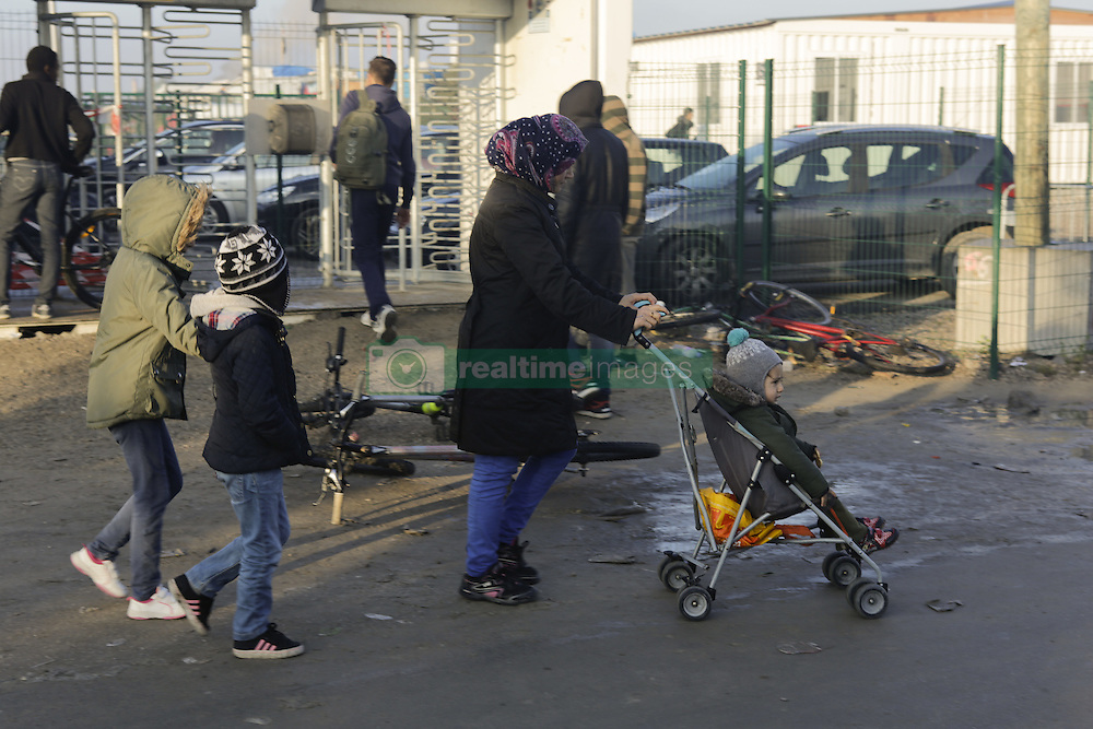 October 25, 2016 - Calais, Nord-Pas-de-Calais-Picardie, France - A woman and her three children walk outside the official container camp. A little less than 2000 refugees are expected to be disbursed from the Jungle to different areas in France on the 2nd day of the eviction of the Jungle in Calais. It is also expected that the demolition of the camp will start. (Credit Image: © Michael Debets/Pacific Press via ZUMA Wire)
