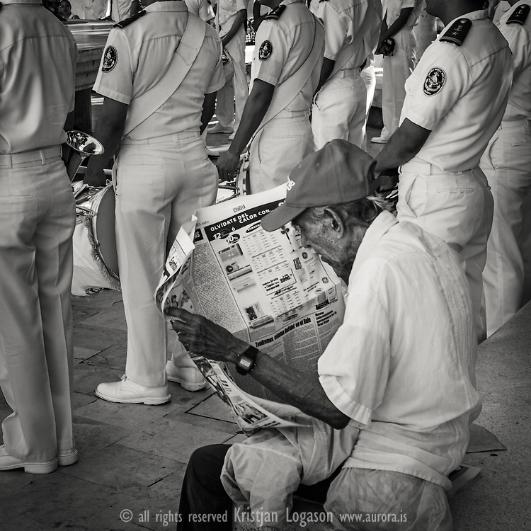 Mann sitting in the central square in veracruz reading his newspaper while the navy marchingband is performing their music
