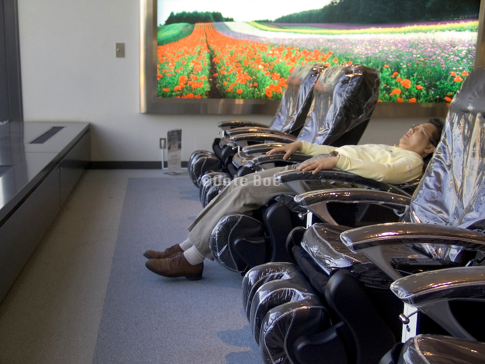a man relaxing in a massage chair with a light box of a landscape view with flowers in the background
