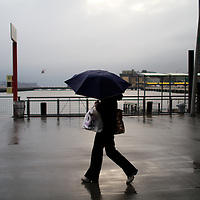 A women with umbrella during rain storm at pier 11 ferry terminal downtown New York City