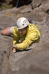 A man lead climbs a thin vertical crack on Beacon Rock, a volcanic plug featuring basalt columns.