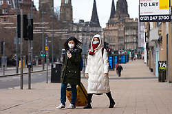 Edinburgh, Scotland, UK. 29 March, 2020. Life in Edinburgh on the first Sunday of the Coronavirus lockdown. Streets deserted, shops and restaurants closed, very little traffic on streets and reduced public transport. Pictured; Princes Street with two women wearing face masks. Iain Masterton/Alamy Live News