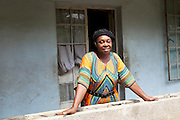 Ijeoma Ewurum outside her home in Nigeria. <br /> <br /> Ijeoma used to keep chickens as a hobby but when she retired from her teaching career she set it up as a larger business. <br /> <br /> She attended a business training workshop with Youth for Technology and signed up to receive Business SMS support.<br /> <br /> The main examples of success and impact from the SMS are around innovation and improving product quality; as a result she invested in new feed and vitamins and now has bigger and better eggs and heavier healthier birds. <br /> <br /> What she valued most from the training was learning about capital – she has not heard that word before but now understands the need to reinvest in your business. From the face to face she also valued meeting other women who offered advice.