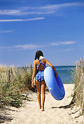 Young girl with inner tube at beach entrance, Cape Cod
