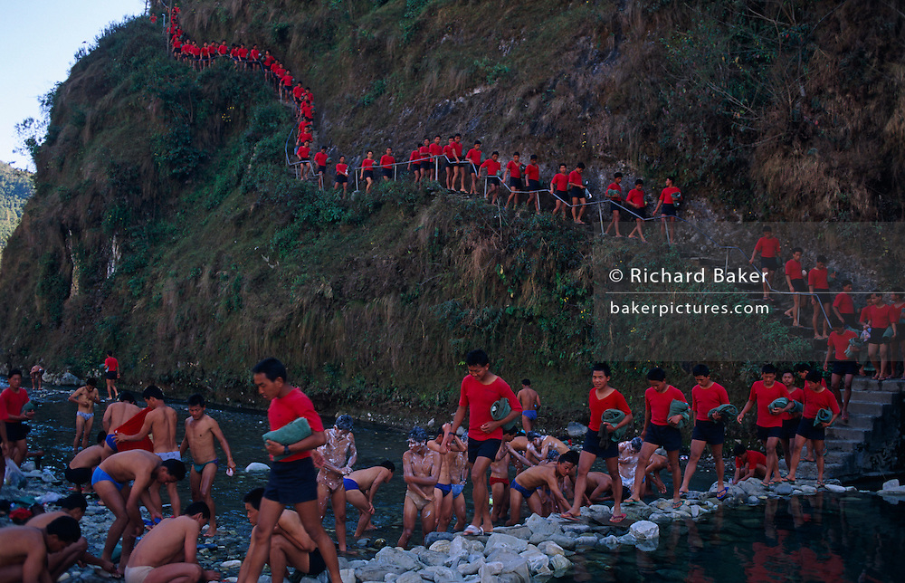 For their regular river washing ritual, the red identical t-shirts of young Nepali boys walk in single-file down a valley side near the British Gurkha Regiment's army camp at Pokhara after recently being recruited into the regiment after a gruelling series of tests to eliminate the weaker and less able candidates. 60,000 boys aged between 17-22 (or 25 for those educated enough to become clerks or communications specialists) report to designated recruiting stations in the hills each November, most living from altitudes ranging from 4,000-12,000 feet. After initial selection, 7,000 are accepted for further tests from which 700 are sent down here to Pokhara in the shadow of the Himalayas. Only 160 of the best boys succeed in the journey to the UK. The Gurkhas have been supplying youth for the British army since the Indian Mutiny of 1857.