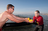 Lifeguard Mark Rathsam hands off some rubber ducks to colleague Rick Schwering during the Ducky Derby in Del Mar on Saturday, October 24.