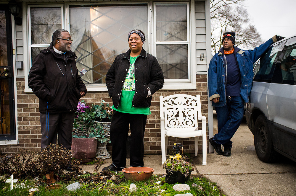 The Rev. Delwyn Campbell, national missionary to Gary, Ind., witnesses with Melody Jefferson and Anthony King at a home in Gary on Wednesday, April 5, 2017. Reflected in the window is the neighborhood parish of St. Philip Lutheran Church. LCMS Communications/Erik M. Lunsford