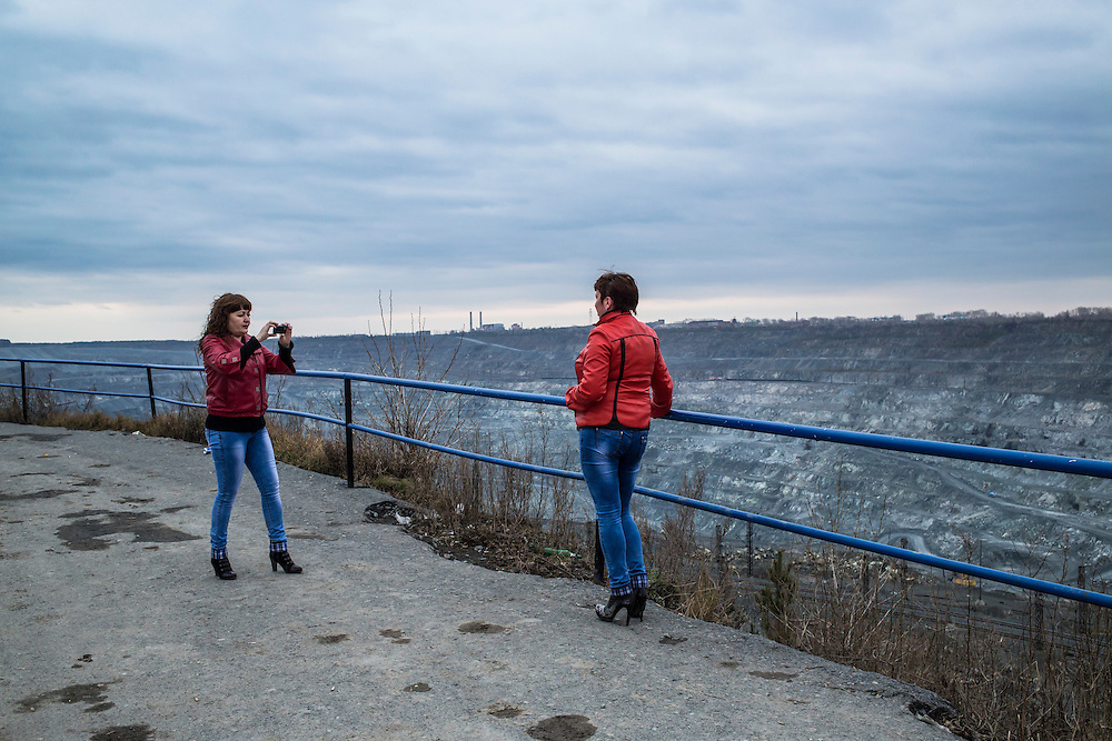 Lilia Orlova, left, photographs Julia Talipova at an observation point along the rim of the Uralasbest asbestos mine on Tuesday, November 12, 2013 in Asbest, Russia. Talipova, a native of Asbest, works in Russia's far east, where she makes several times the prevailing wage back home. When she returns she visits the hole, as it's called locally, because she says she misses it. The mine is among the largest producers of the chrysolite form of asbestos in the world.