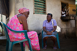 Rosa Diego, right, visits Ignacia Lambert, a woman with HIV, at her home on January 15, 2013 in San Juan, Honduras. Rosa is a community health worker who visits people with HIV in order to check up on them, and to offer assistance and support.  (David Rochkind/ Pulitzer Center)