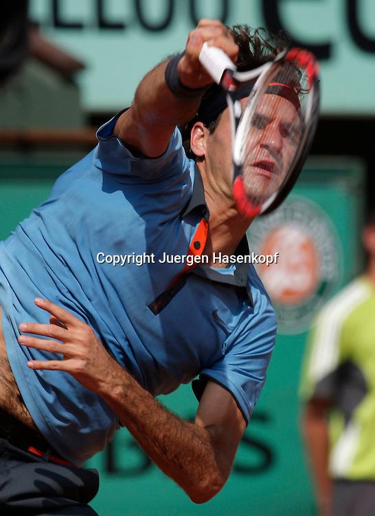 French Open 2009, Roland Garros, Paris, Frankreich,Sport, Tennis, ITF Grand Slam Tournament,  <br /> Roger Federer (SUI) spielt einen Aufschlag,service,action,kurios,Gesicht hinter Saiten<br /> <br /> Foto: Juergen Hasenkopf