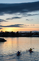 Kayakers paddle towards the sunset in the Inner Harbour of Victoria, BC.