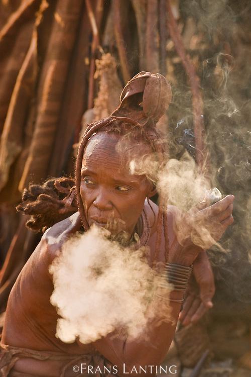 Himba woman smoking tobacco, Puros Conservancy, Damaraland, Namibia