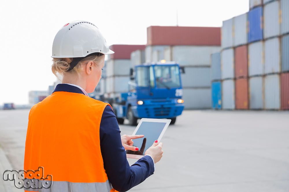 Rear view of female engineer using tablet PC in shipping yard
