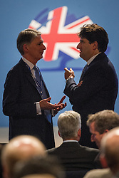 © Licensed to London News Pictures . 29/09/2013 . Manchester , UK . Philip Hammond talks with Lord Andrew Feldman in the auditorium . Day 1 of the Conservative Party Conference at Manchester Central . Photo credit : Joel Goodman/LNP