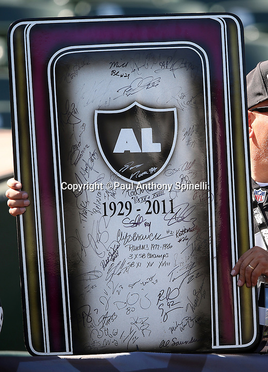 An Oakland Raiders fan holds up a signed plaque dedicated to deceased Raiders owner Al Davis during the 2015 NFL week 5 regular season football game against the Denver Broncos on Sunday, Oct. 11, 2015 in Oakland, Calif. The Broncos won the game 16-10. (©Paul Anthony Spinelli)