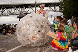 North America, United States, Washington, Seattle, woman pushing ball of plastic containers during annual Summer Solstice Parade in Fremont neighborhood