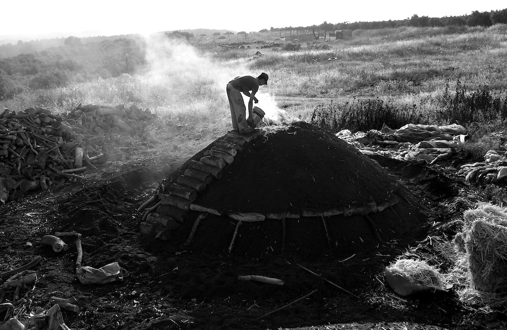 Hadder Kabah  17 working at the charcoals factory in the Arab Israeli village of  Arra ,..Hader weak up in the morning checking the fire in the pile of wood and if it to high he pour water in to take it down and if it low he put straw to make it higher.....Hadder is a Palestinian that got this job with his older brother he is illegal in Israel so he can?t go back home at the end of the day hi stay in the place and watch the fire....Monday April 5, 2008,..