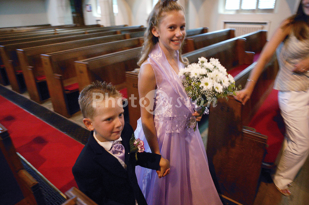 Bridesmaid and pageboy walking down church aisle smiling,