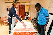 Woluwe-Saint-Lambert. 20 februari 2013 Jongeren bezig met houtsnedes in jongerencentrum Antichambre asbl - Zij zullen na het drukken van de houtsnedes op grote vellen papier, in het mim, muziekinstrumentenmuseum , een performance ondersteunen tijdens de museum nightfever. De meester legt uit wanneer inkt goed dekt.