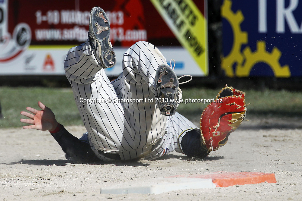 Japan's Tadaaki Saeki takes a tumble after a clash at first base. 2013 ISF Mens World Softball Championship, Pool Match, New Zealand Black Sox v Japan, Rosedale Park, Albany, New Zealand. Sunday 3rd March 2013. Photo: Anthony Au-Yeung / photosport.co.nz
