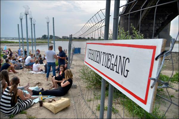 Nederland, Nijmegen, 16-7-2015 Recreatie, ontspanning, cultuur, dans, theater en muziek in de binnenstad tijdens het zomerfestival de Kaaij. Vooral tijdens de zomerfeesten een gewilde plek om te ontspannen.Dit jaar is het door de gemeente verboden te zwemmen in het stuk van de rivier de waal wat grenst aan het terrein. Er is een hek geplaatst. Men vindt het risico op aansprakelijkheid te groot. Het alternatieve en relaxte terrein onder de Waalbrug van festival de Kaay waar eten en drinken, verschillende soorten live muziek en zitten bij het water van de rivier de Waal de leukste dingen zijn. Foto: Flip Franssen/Hollandse Hoogte