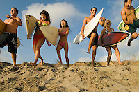 Six surfers carrying surfboards running on beach low angle view