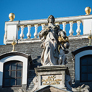 A statue sitting on top of one of the ornate buildings on Grand Place (La Grand-Place), a UNESCO World Heritage Site in central Brussels, Belgium. Lined with ornate, historic buildings, the cobblestone square is the primary tourist attraction in Brussels.