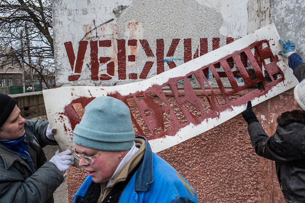 MARIUPOL, UKRAINE - FEBRUARY 5, 2015: A stencil is used to paint directions to a bomb shelter on the side of an apartment building in Mariupol, Ukraine. On January 24, a number of rockets landed just across the street, killing 31 people and injuring over 100. With more than 220 people having died in the past several weeks, a new diplomatic push is underway to bring an end to fighting between pro-Russia rebels and Ukrainian forces. CREDIT: Brendan Hoffman for The New York Times